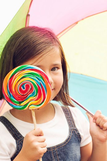 Stock Photo: 1566-524082 girl plays peek-a-boo with lollipop in the rain