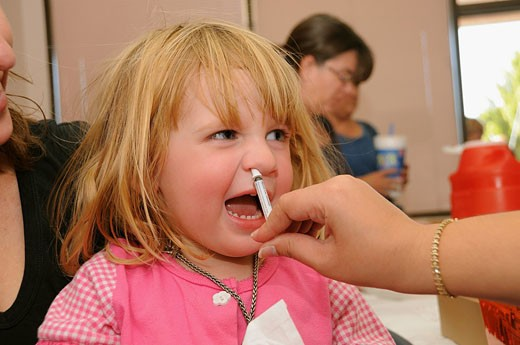 Stock Photo: 1566-524209 A 4-year-old girl is vaccinated for the 2009 H1N1 influenza, also known as the Swine Flu, with a live, attenuated intranasal vaccine nasal spray vaccine at the Pima County Health Department, Tucson, Arizona, USA