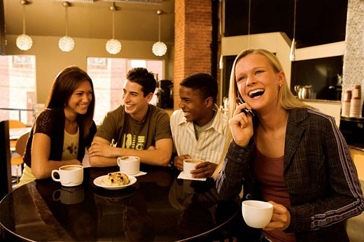 Teens hanging out in coffee shop. : Stock Photo