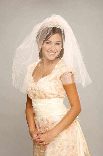 Stock Photo: 1566-528295 Bride in her 20s smiles at the camera in a studio setting