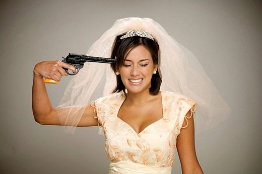 Bride points a gun to her head : Stock Photo