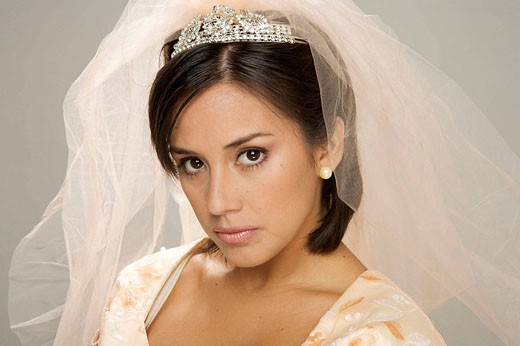Bride in her 20s looks at the camera angry : Stock Photo