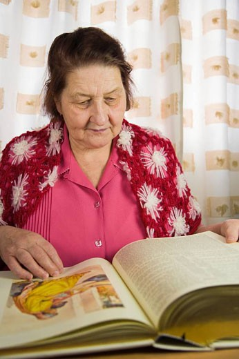 67 years old woman reading bible : Stock Photo