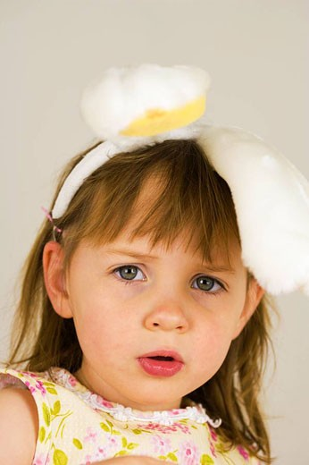 Stock Photo: 1566-528808 Portrait of 3 year old girl with bunny ears