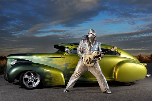 Stock Photo: 1566-529090 Silver Elvis with a guitar standing in front of a custom lowride Studebaker hot rod under dramatic sunset sky  Performing artist Peter Jarvis from Toronto Canada