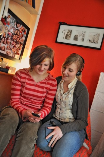 zwei junge Frauen in ihrem Zimmer mit Handy und MP3-Player , two young women in their room listening to music from an MP3 player and playing with a mobile phone : Stock Photo