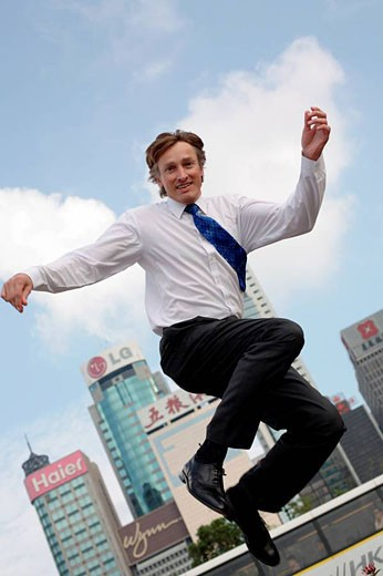 Full body photograph of young, caucasian business man in business atire, jumping, with highrise office buildings in the background, Hong Kong, China, Asia : Stock Photo