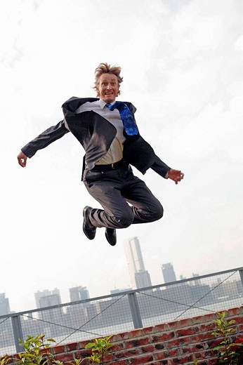 Stock Photo: 1566-531639 Full body photograph of young, caucasian business man in business suit, jumping over a fence, with highrise office buildings in the background, Hong Kong, China, Asia