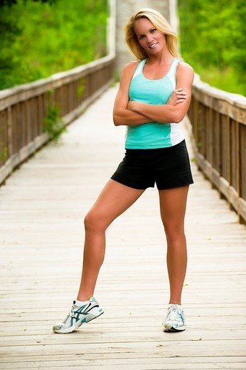 Stock Photo: 1566-539234 30 year old blonde woman in work out clothes standing straight and looking at camera