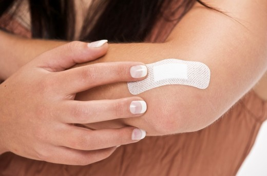 young woman with adhesive sticking on her elbow for a slight wound : Stock Photo