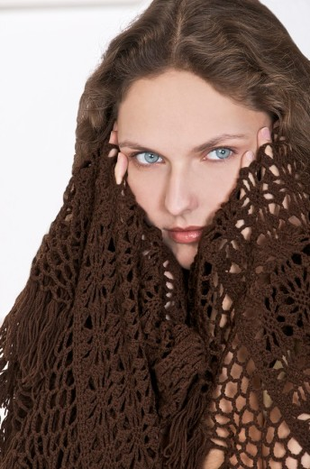 young woman in a brown shawl,holding her temples because of  a headache : Stock Photo