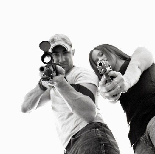 Stock Photo: 1566-541287 Man and women with guns; aiming at lens.