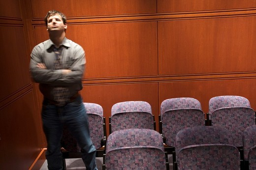 Stock Photo: 1566-542198 Young man alone in an auditoriam