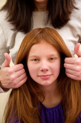 Mother fixing the hair of her preteen redhead daughter : Stock Photo