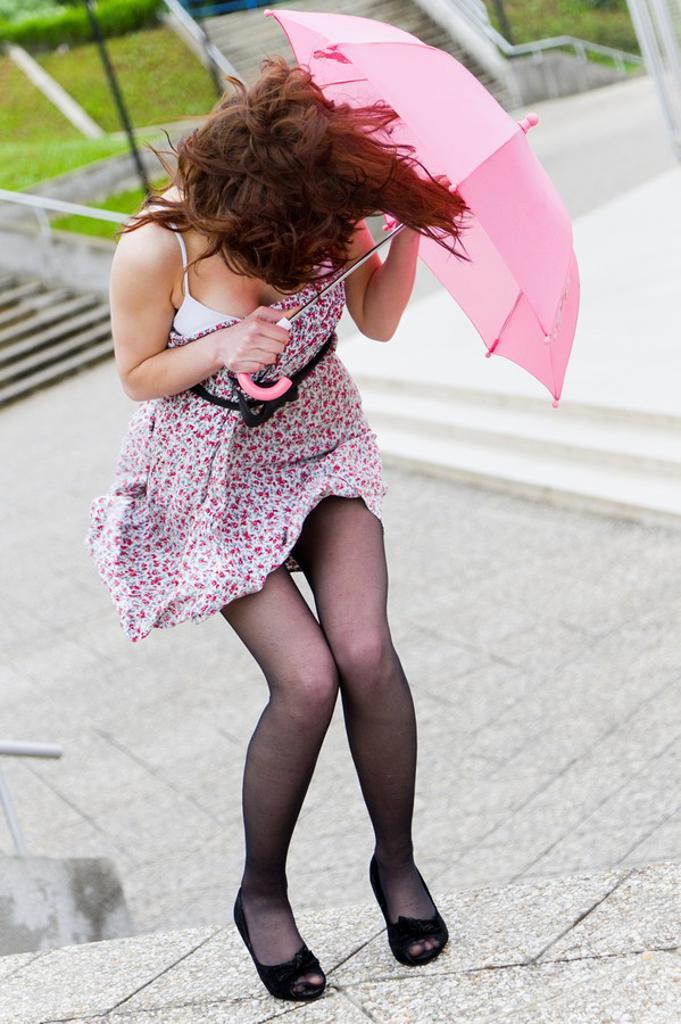 Protecting under small pink umbrella : Stock Photo