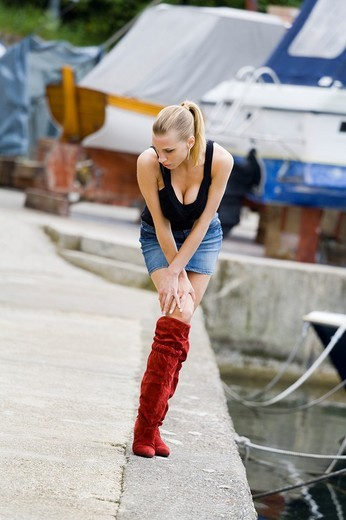 Posing in the hatbour sexy woman in Red boots : Stock Photo