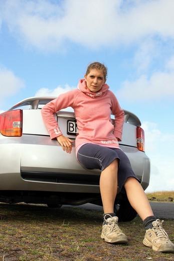 A woman pushing a broken down car : Stock Photo