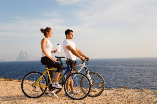 Couple with bikes looking at the horizon in a cliff by the sea : Stock Photo