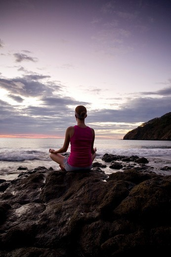 Stock Photo: 1566-544544 Young woman meditating on rocks at sunset in front of ocean surf at Playas del Coco, Costa Rica