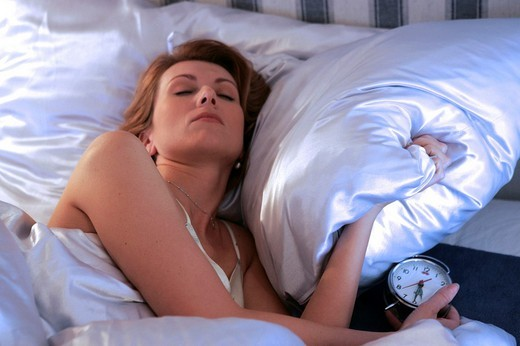 Woman awaking by alarm clock in the morning : Stock Photo