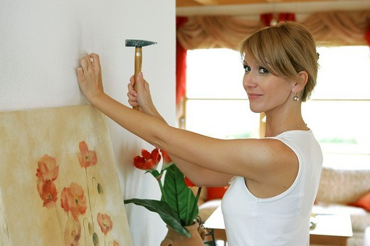 woman hanging up a painting : Stock Photo