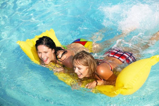 two women having fun with air mattress in the pool : Stock Photo