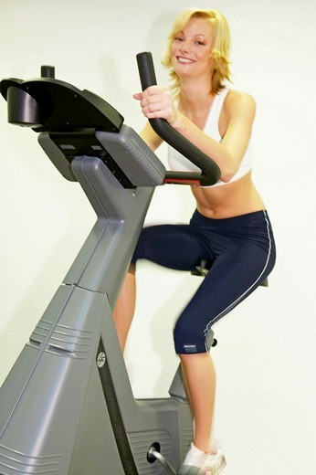 Stock Photo: 1566-549390 Young woman in Fitness Studio training on bike simulator Spinning