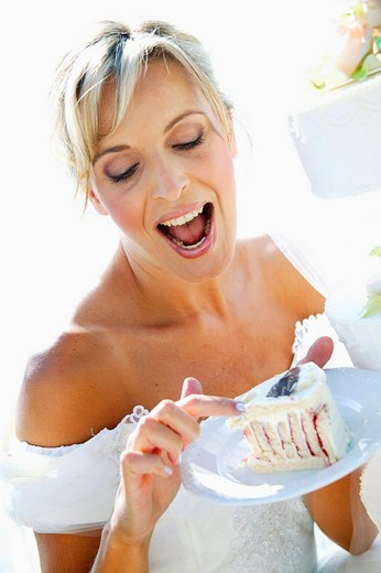 Stock Photo: 1566-549463 young bride nibbles at the wedding cake