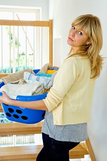 Stock Photo: 1566-549872 young woman with laundry basket