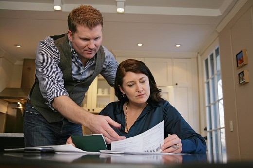 Husband is angry as married couple pays their bills and reviews their finances together : Stock Photo