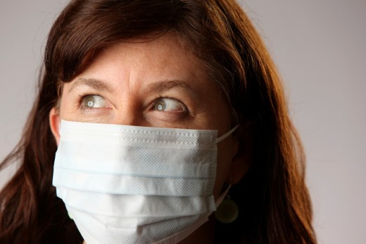 Woman wearing surgical mask to protect herself from contracting contagious influenza viruses like H1N1 Swine Flu : Stock Photo