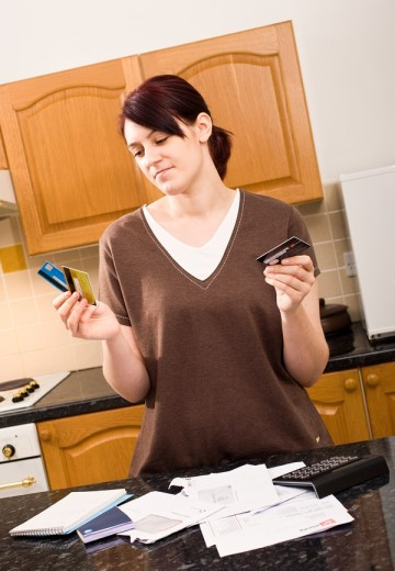 Stock Photo: 1566-550073 Young woman choosing which credit card bill to pay first - MR & PR