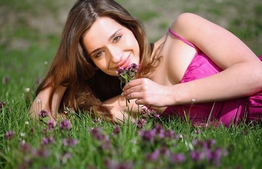 Stock Photo: 1566-550386 frau,liegt,liegen,liegend,wiese,blumenwiese,blumen,blueten,fruehlingsblumen,fruehling,gras,natur,landschaft,sonne,sonnen, sonnenstrahlen,sonnig,geniessen,geniesst,relaxen,relaxt,ausruhen,sonnenschein,gesicht,entspannt,entspannung,fruehjahr, lila,pink,bunt