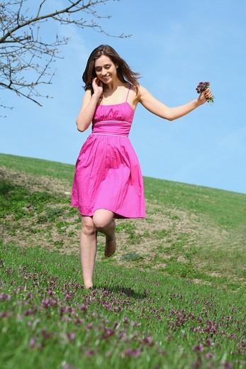 Stock Photo: 1566-550402 frau,liegt,liegen,liegend,wiese,blumenwiese,blumen,blueten,fruehlingsblumen,fruehling,gras,natur,landschaft,sonne,sonnen, sonnenstrahlen,sonnig,geniessen,geniesst,relaxen,relaxt,ausruhen,sonnenschein,gesicht,entspannt,entspannung,fruehjahr, lila,pink,bunt