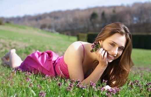 Stock Photo: 1566-550413 frau,liegt,liegen,liegend,wiese,blumenwiese,blumen,blueten,fruehlingsblumen,fruehling,gras,natur,landschaft,sonne,sonnen, sonnenstrahlen,sonnig,geniessen,geniesst,relaxen,relaxt,ausruhen,sonnenschein,gesicht,entspannt,entspannung,fruehjahr, lila,pink,bunt
