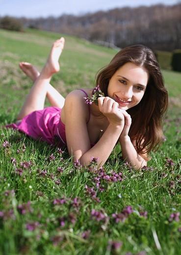 Stock Photo: 1566-550414 frau,liegt,liegen,liegend,wiese,blumenwiese,blumen,blueten,fruehlingsblumen,fruehling,gras,natur,landschaft,sonne,sonnen, sonnenstrahlen,sonnig,geniessen,geniesst,relaxen,relaxt,ausruhen,sonnenschein,gesicht,entspannt,entspannung,fruehjahr, lila,pink,bunt