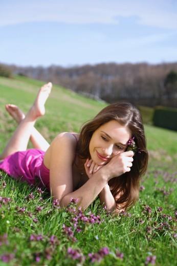 Stock Photo: 1566-550415 frau,liegt,liegen,liegend,wiese,blumenwiese,blumen,blueten,fruehlingsblumen,fruehling,gras,natur,landschaft,sonne,sonnen, sonnenstrahlen,sonnig,geniessen,geniesst,relaxen,relaxt,ausruhen,sonnenschein,gesicht,entspannt,entspannung,fruehjahr, lila,pink,bunt
