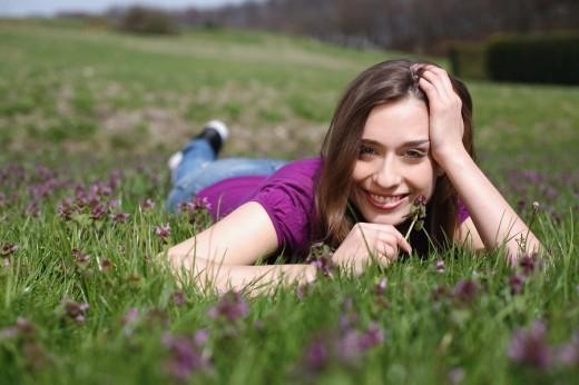 Stock Photo: 1566-550419 frau,liegt,liegen,liegend,wiese,blumenwiese,blumen,blueten,fruehlingsblumen,fruehling,gras,natur,landschaft,sonne,sonnen, sonnenstrahlen,sonnig,geniessen,geniesst,relaxen,relaxt,ausruhen,sonnenschein,gesicht,entspannt,entspannung,fruehjahr, lila,pink,bunt