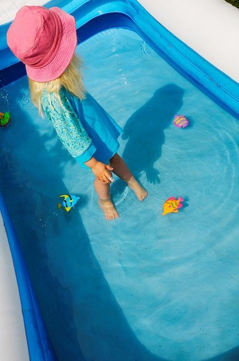 Stock photo of a 3 year old girl dressed in a hat and protective clothes against the sun playing in a paddling pool : Stock Photo
