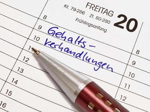 A calendar shows March the 20th, the item salary negotiations is in the calendar written with german words. Beside is a pen : Stock Photo