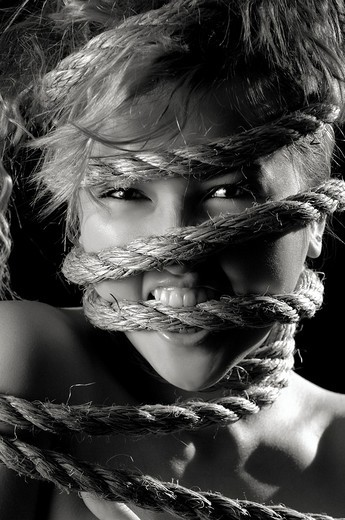Conceptual artistic portrait of a young beautiful woman with her face tied in ropes Biting them with emotional angry aggressive expression Black-white sepia toned : Stock Photo
