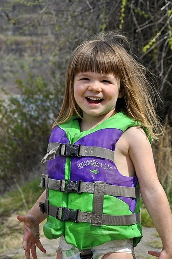 This cute 3 year old Caucasian girl is smiling and happy while playing outdoors  She´s wearing a green life vest and coverd in mud as she´s been playing : Stock Photo