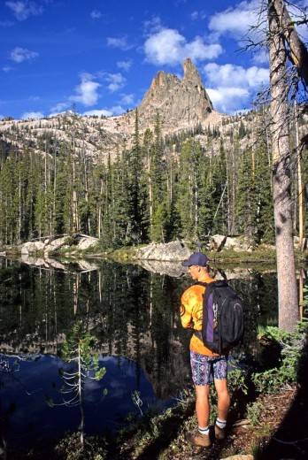 Stock Photo: 1566-556411 Ron Veldink, pauses at a small lake while hiking to The Finger Of Fate for a rock climb of The Open Book route in the Sawtooth Mountains, Idaho
