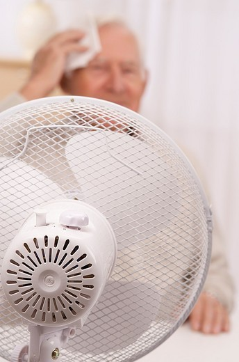 Senior man wiping his forehead with a fan, during hot period : Stock Photo