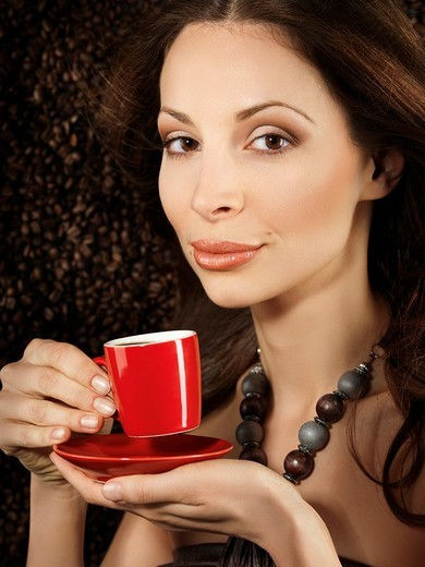 Stock Photo: 1566-556825 Beautiful young woman holding a red cup of espresso coffee with coffe beans background behind her