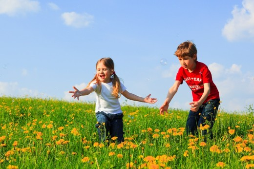 Stock Photo: 1566-558120 boy and girl playing with bubbles in field of Dandelions,Zuercher Oberland, Zuerich, Switzerland
