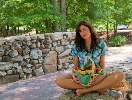 32 year old brunette woman in casual summer dress sitting cross-legged on a stone wall holding a basket of mixed vegetables. : Stock Photo
