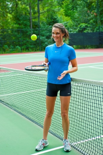Stock Photo: 1566-558484 25 year old brunette woman on a tennis court playing with racquet and ball