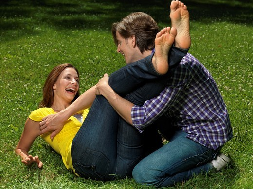 Young happy couple in their early thirties having fun in the nature on green grass  Young man tickling laughing young woman´s bare feet : Stock Photo