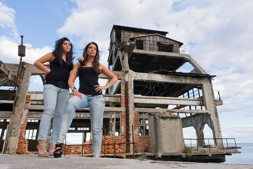 Stock Photo: 1566-559633 Two girlfriends are posing next to a derelict building remains of a torpedo testing station in Rijeka, Croatia